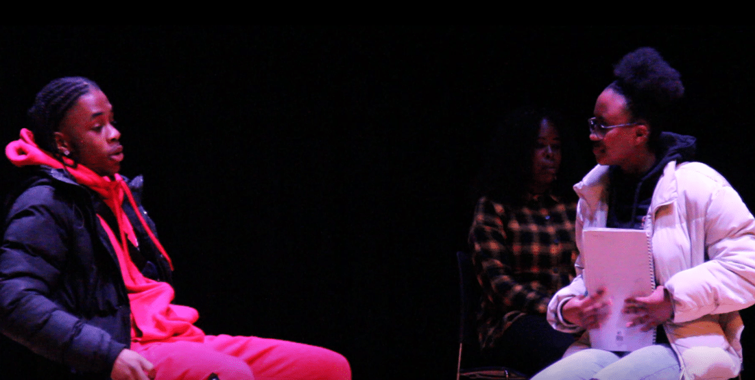 Two of the Drilling Diamonds actors in performance. Boy sitting on the left wearing a red tracksuit being questioned by a girl sitting down on the right holding a notepad