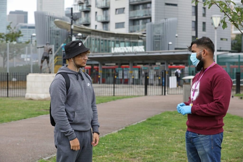 Outreach youth worker talking to young person Credit: Rehan Jamil